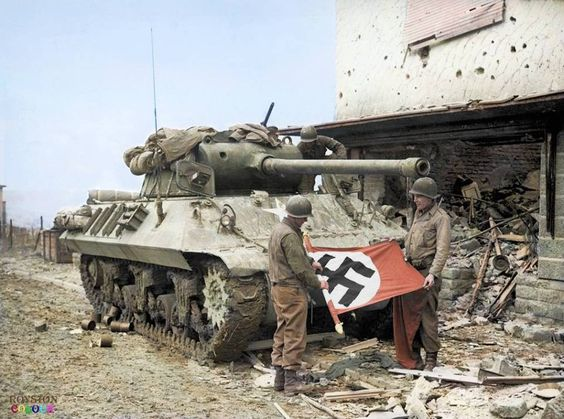 The American crew of this M36 90mm Tank Destroyer (90 mm Gun Motor Carriage) are seen here rolling up a Swastika flag they had found in the German town of Bitburg. The town was captured on February 28 1945.