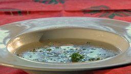 Eine klare Hühnerbrühe in einem weißen Suppenteller.
