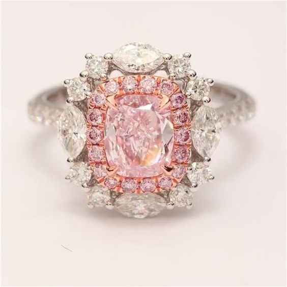 A fancy pink cushion surrounded by a pink halo, set in rose gold. White Marquise and round diamonds add a beautiful touch, and the detailing on the back completes it. .