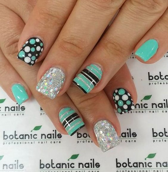 Sea green and black themed spring nail art design. Make sure your nails truly stand out with this quirky design of stripes and polka dots. Bring more attitude to your nails with silver glitter polish.