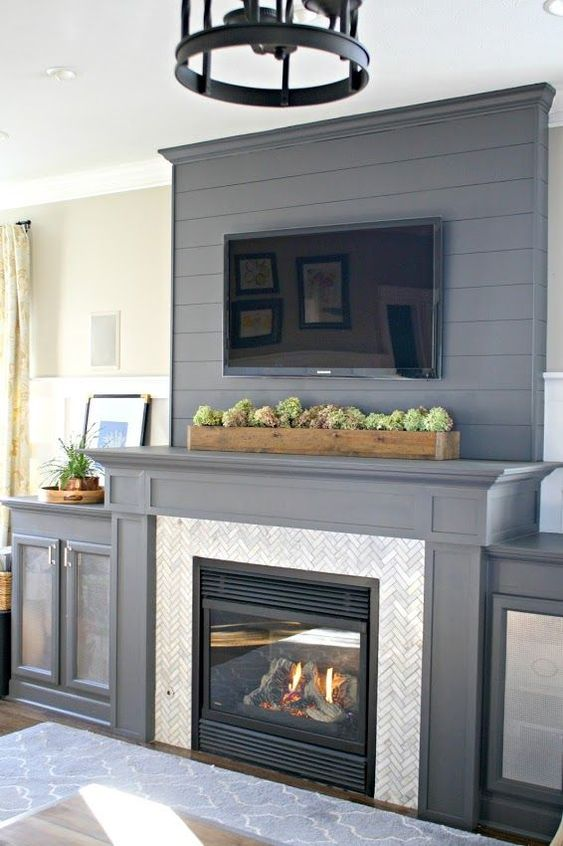 Shiplap above fireplace with marble tile surround