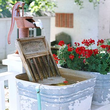 Rustic Appeal are these salvaged treasures, like this water pump, washboard, and galvanized bucket, provide this Victorian farmhouse with plenty of down home charm. Bundle of red geraniums looks so pretty with these things of the past!!