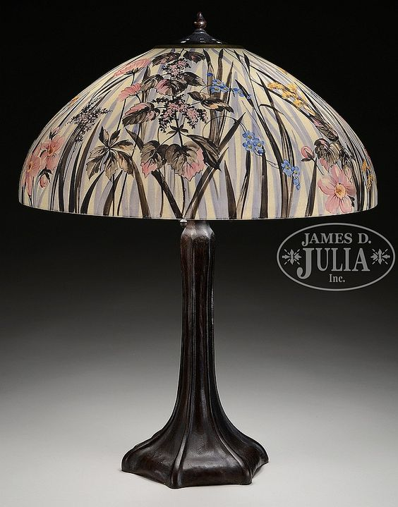 "Handel table lamp has dome shaped shade that is obverse painted with wild flowers surrounding the entire shade. Flowers are done in pink, blue and yellow with brown, green and gray leaves extending from bottom to top of shade against an acid textured white background. Signed inside rim ""Handel 6931"". Shade rests on a Handel base with vertically ribbed foot and stem. Base has a 3 socket cluster and heat cap with square cutouts. Signed on the underside with impressed block letters ""Handel"". Sh..."
