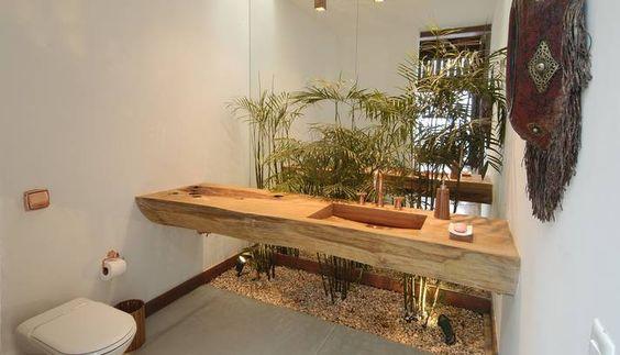 Palmeiras e pia de madeira dão ar rústico a banheiro de residência em Angra. O espelho atrás da pia dobra a planta, que neste caso foi plant...