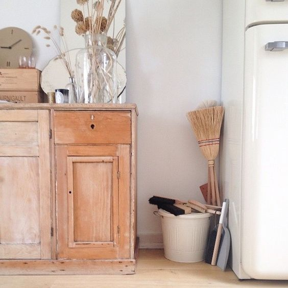 Country kitchen with wood sideboard. A woman after my own heart- she buys brooms and brushes in every country she visits. Lucille Gauthier-Braud's kitchen in Paris.