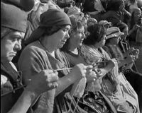 Film still of women knitting while watching the beheadings of the revolution.