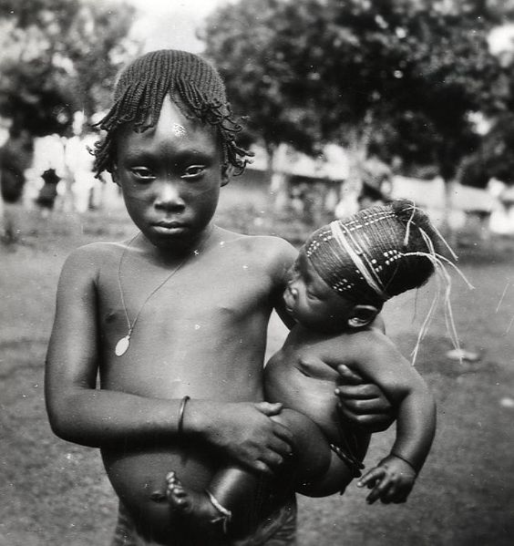 A young Mangbetu girl carrying a baby -1949  © Marcolin