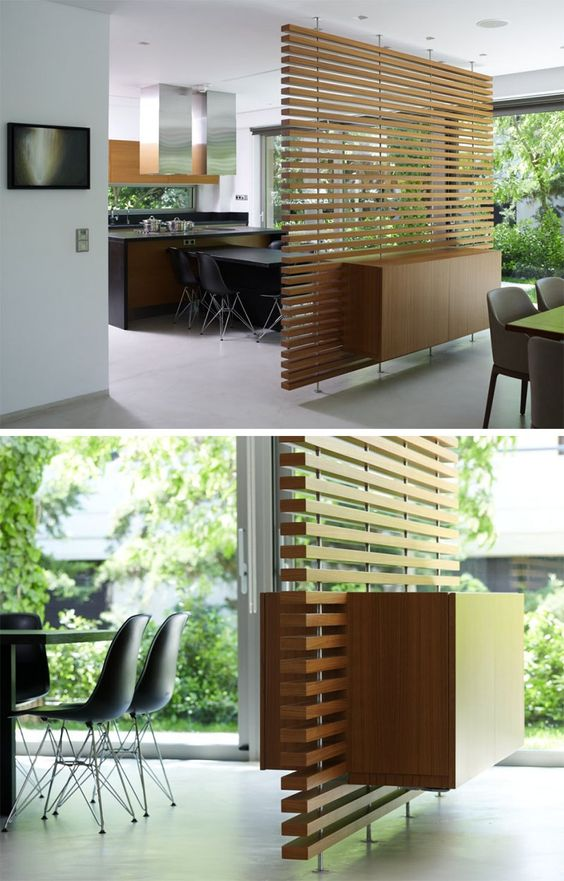 This slatted wooden room divider has a built-in cabinet.