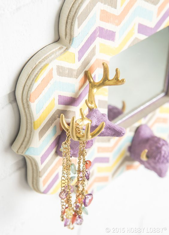 We sawed down a trio of antlered animal figurines (right at the shoulders) to make this conversation-starting piece. Then we painted them and mounted them on a hand-stenciled wooden picture frame. A little craft mirror, glued to where the photo would go—and a jewelry organizer was born!