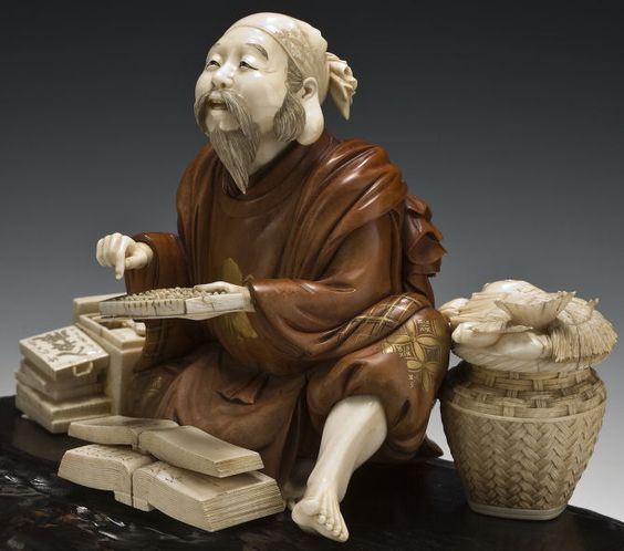 A beautiful okimono of Ebisu in the role of a shopkeeper, seated with his left leg cossed, gazing up from a soroban, two account books placed before him, flanked by a suzuribako on his left and a basket of fish at his right, signed Toshimune.