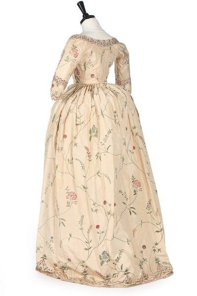 1770s - Painted silk robe à la polonaise, English. The ivory silk painted to shape in imitation of Chinese silk, with closed front bodice, the edges and front openings painted with foliate swags with delicate meandering buds and wild flowers over the ground, with cord polonaise ties and loops within the overskirt the petticoat painted to match and lined in wool