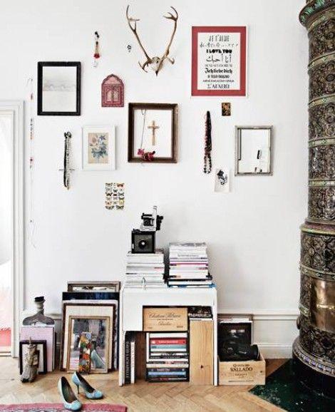 Un salón inspirador. Salamadra , marcos en la pared y libros apilados