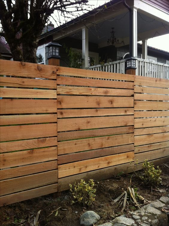 Horizontal fence with various size boards into the for Garden decking and fencing