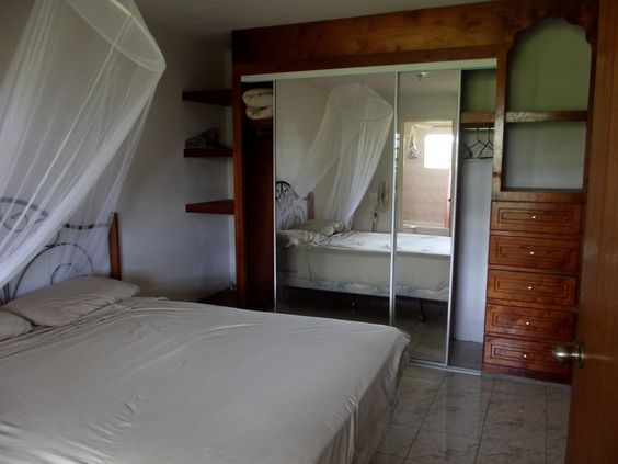A large separate bedroom with a queen sized bed and a closet with the bathroom just off to the left.