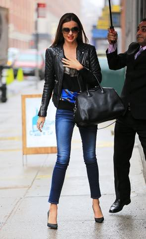 Chiodo di pelle e tacchi per Miranda Kerr, comodamente scortata sotto l'ombrello fino al taxi a New York.. Foto-gallery e immagini