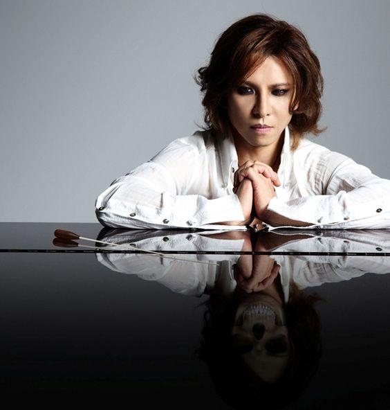 ピアノの上に腕を置いている白いシャツを着たXJAPAN・YOSHIKIの画像