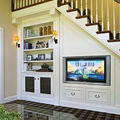 The depth of space under a staircase can be sufficient for a built-in entertainment center that houses a flat-screen TV and a bookcase to boot, along with drawers for remotes, movies, and game accessories.: