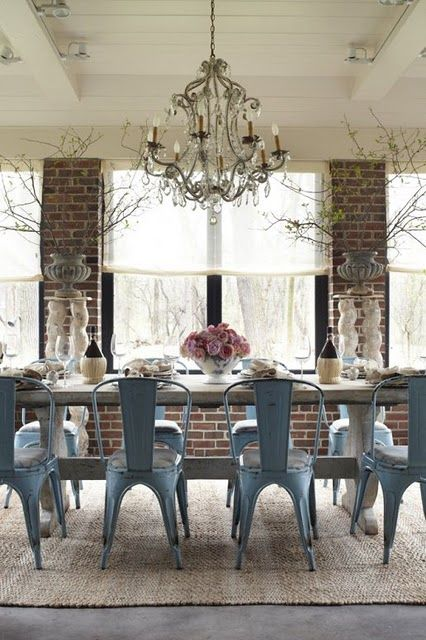 More tolix chairs. Love the slate blue, rustic table, brick walls, wood planked ceiling, and chandelier.: