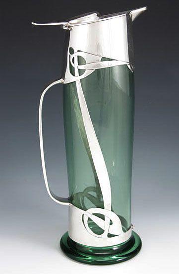 Liberty & Co.   Designer Archibald Knox   Description Magnificent silver & glass claret jug   Country of Manufacture England   Date 1902