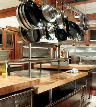 Beautiful commercial kitchen, the stainless steel appliances and shelves make the wooden countertops stand out and brighten up the entire commercial kitchen.