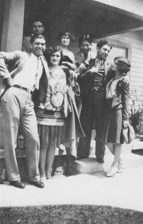 Stylish family posing on the porch in front of a house on Judson Street in Boyle Heights. Lower row, left to right: Frank Miranda and Caroline Miranda, aunt of Hortensia Corral. Top row, left to right: a family friend, Emma Cann, aunt of Hortensia Corral, and family friend. On stairs, left to right: Emilio Marquez and Elouise Marquez who baby-sat Hortensia Corral.