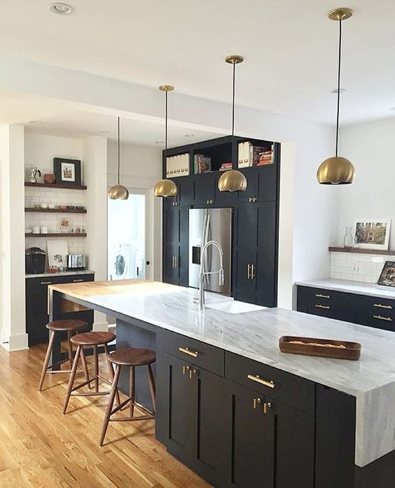 Brass lighting, matte cabinets, marble waterfall counters.