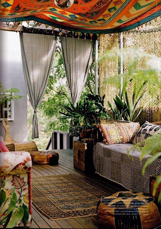 Bohemian patio.  Lush potted plants and beautiful fabrics.  Love!
