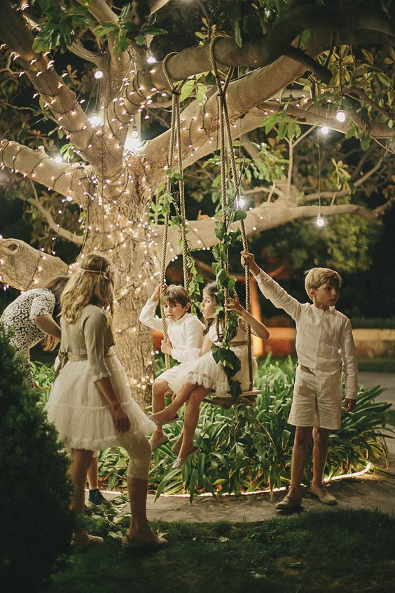 Children on a Fairy light garden swing | Destination wedding in Castellón Spain, near the Mediterranean Sea | Pastel colour scheme | DIY decor | Images by Volvoreta Bodas | http://www.rockmywedding.co.uk/adri-igor/: