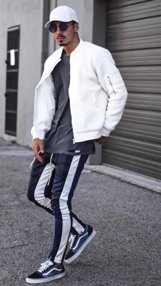 hombre con sudadera bicolor, tenia a juego, camiseta con un roto, chaqueta y gorra blancos