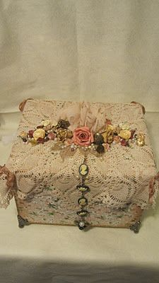 A crochet wrap over gift wrap paper!!! Bebe'!!! Trimmed with av row of pearls, beads, and silk flowers and trailing a black and white cameo bracelet!!!