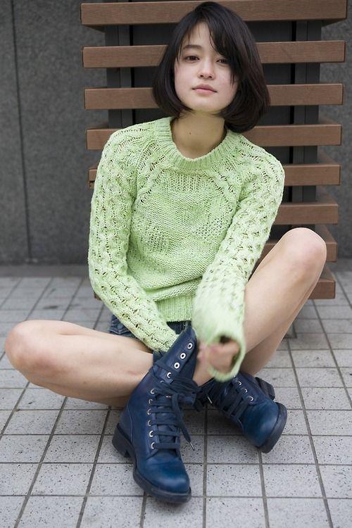 グリーンのセーターを着た地面に座っている小林涼子の画像