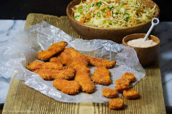 Krokante kip nuggets zonder frituurpan, gebakken in de oven. Een Japanse smaak door de coating van pittige rijstzoutjes. Lekker met coleslaw.
