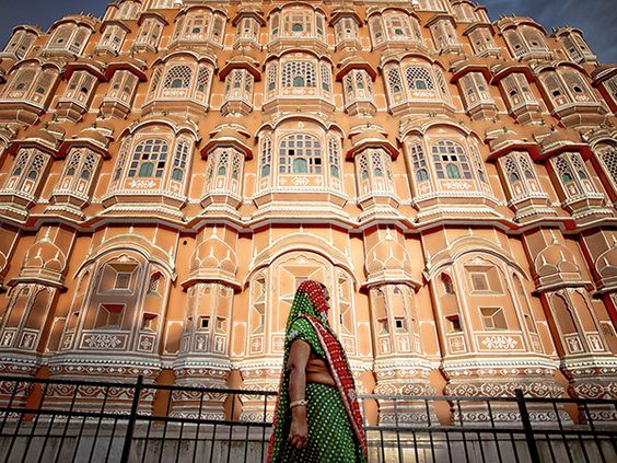 """Palace of the Winds, India Photograph by Ruzely Abdullah, National Geographic Your Shot  A woman stands in front of the pink sandstone walls of Hawa Mahal, or """"Palace of the Winds,"""" in Jaipur, India."""