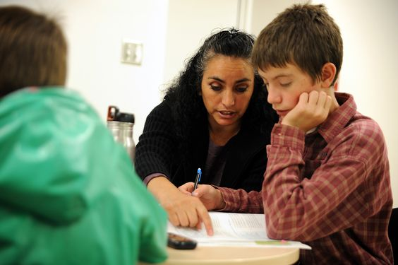 Maria Enright assists her eighth grade son, Joseph Enright, 13, with a math assignment Sept. 12 at Falcon Virtual Academy in Colorado Springs. She has five children enrolled in the academy, from third to ninth grade. The kindergarten-twelfth grade multidistrict public school had just opened its new 21,000 square-foot state-of-the-art facility, which tripled its physical space and increased its Internet bandwidth.