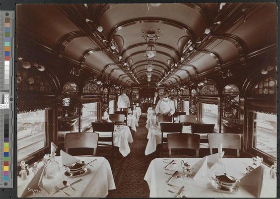 Dining car, with tables set and waiters standing behind chairs, on the Erie Railroad.