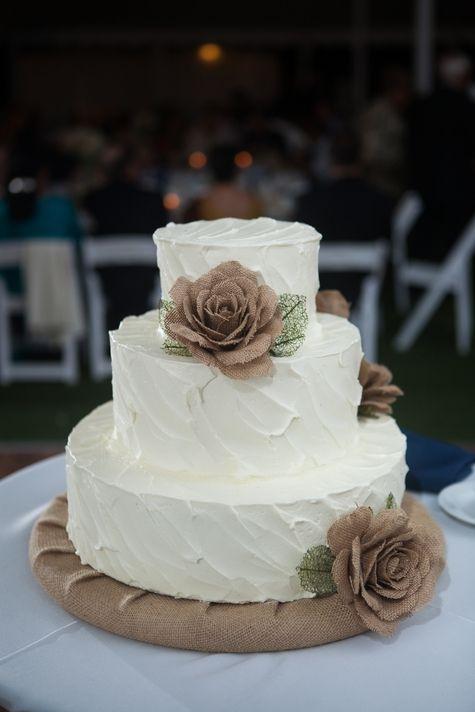three tiered white wedding cake with burlap flowers