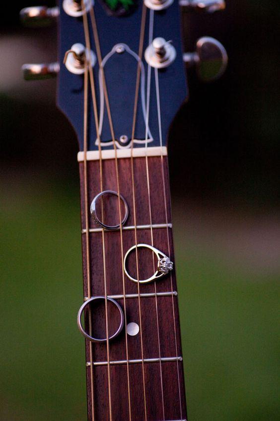 Wedding rings held by guitar.