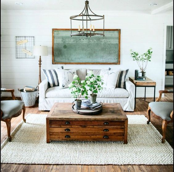 Beautiful living room with white couch, woven rug, green plants, white and blue striped pillows, wood apothecary coffee table, chalkboard wall decor, hanging iron light pendant.