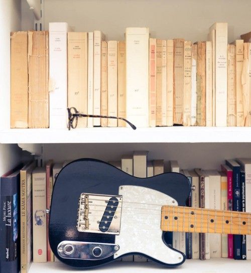 white books on a bookshelf. electric guitar.