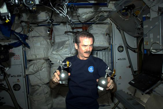 """Canadian astronaut Chris Hadfield holds up two objects that look like grenades as part of an April Fools' Day prank. (Credit: Canadian Space Agency/Chris Hadfield ) April 1, 2013. ( They're actual air sampling devices.) Mona Evans, """"Astronomy April Fools"""" http://www.bellaonline.com/articles/art183019.asp"""