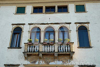 Photo made in an elegant building located in the right bank of the river Brenta at Oriago a town in the province of Venice in the Veneto (Italy). In the image you see the balcony with stone balustrade supported by columns on which are supported the flower pots. In addition to the triple lancet window and arch there are two windows along the side with the shutters closed.
