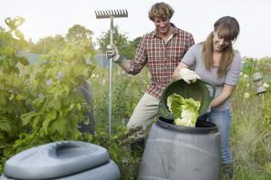 Couple working in allotment depositing waste into recycling compost bin. - Mike Harrington/Taxi/Getty Images