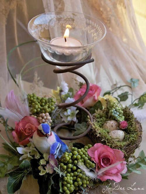 Votive with rusty spring in a floral centerpiece
