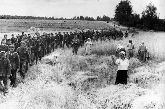 German prisoners of war marching east under the supervision of Soviet soldiers, 1944. Take note of the Soviet woman showing a 'dulya' with her hand to the Germans as they pass by.