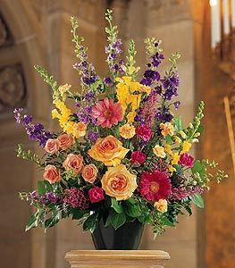 This outstanding arrangement of vibrant seasonal flowers offers your condolences in a most memorable way. A mixture of hot pink gerberas, peach carnations and spray roses, purple larkspur and yellow snapdragons in a green jardiniere.