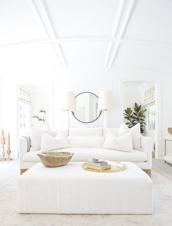Design inspiration from this all white living space with white linen sofa, upholstered ottoman, rustic dough bowl, brass accents, and California modern farmhouse chic by Erin Fetherston.