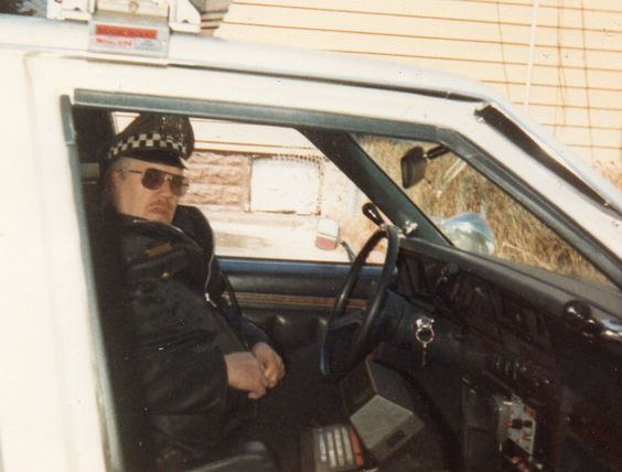 My dad in the alley at our old house in his police car.