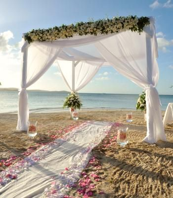 Wedding canopy draped in sheer white fabric and covered with flowers
