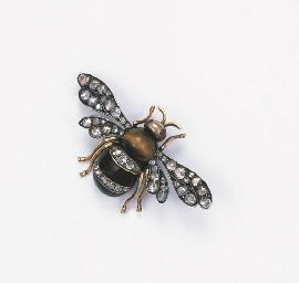 AN ANTIQUE RUSSIAN BEE BROOCH  The tiger's eye and onyx body with diamond line detail to the ruby eyes and rose-cut diamond wings, mounted in silver and gold, circa 1870: