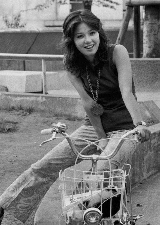 ベルボトムのデニムを履いて自転車に座っているひし美ゆり子の画像